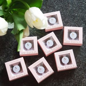 A selection of See Beauty false eyelashes in a pink box and on a dark background